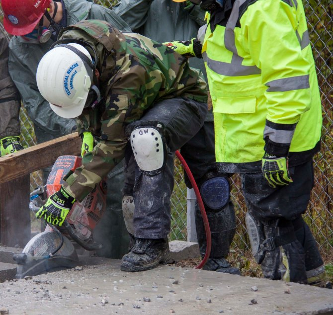 A MA-TF1 team member cuts through concrete with a K-12 rescue saw during an 80 hour structural collapse course in Beverly, Mass. Being well-versed in these tools helps rescuers make their way through debris from collapsed buildings to find survivors. Photo by Eilis Maynard - Oct 24, 2014 - Location: beverly, MA