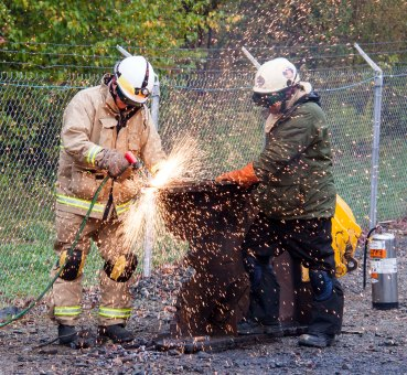 """Members of the Massachusetts Task Force 1 Urban Search and Rescue team cut steel with an exothermic torch during training in October. Team members work in groups of two - a """"burner"""" and a """"tender"""" for safety and accuracy. Photo by Eilis Maynard - Oct 24, 2014 - Location: Beverly, MA"""